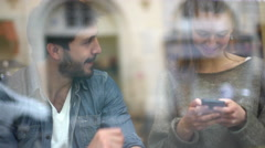 Affectionate couple relaxing in cafe, viewed through window Stock Footage