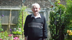 4K Portrait of cheerful elderly man standing in the garden at home. - stock footage