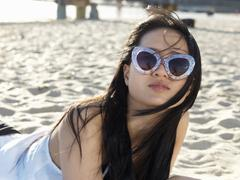 Portrait of young woman on beach in funky sunglasses, Port Melbourne, Melbourne, - stock photo