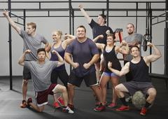 Portrait of eight crossfit colleagues flexing muscles in gym Stock Photos