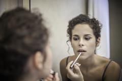 Young woman applying lip gloss Stock Photos