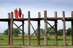 Amarapura, Myanmar - 28 June, 2015: Two monks in colorful robes walk on woode Stock Photos