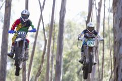 Two young male motocross riders jumping mid air through forest - stock photo