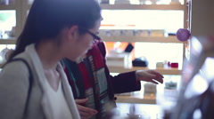 Young women chatting as they browse in shop - stock footage