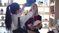 Young women trying on hats together in store - stock footage