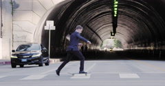 Slow motion business man rides skateboard across city street 4K Stock Footage