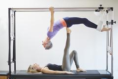 Two mature women practicing pilates on trapeze table in pilates gym Stock Photos