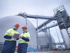 Workers using digital tablet at biomass facility Stock Photos