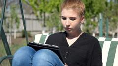 Girl sitting in garden swing using tablet Stock Footage
