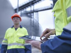 Workers using digital tablet at biomass facility, close up Stock Photos