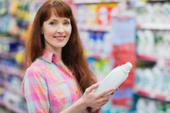 Portrait of woman holding detergent Stock Photos