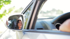 Couple having conversation in car, reflected in side-view mirror Stock Footage