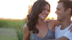 Young couple embracing and talking outdoors Stock Footage