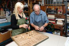 Senior man and young woman assembling book letterpress in traditional - stock photo