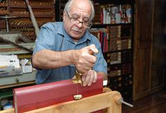 Senior man applying gold leaf to book spine in traditional bookbinding workshop - stock photo
