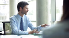 Businessman advising client in office Stock Footage
