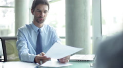 Businessman consulting client in office - stock footage