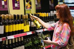 Consumer hesitating between two bottles of wine - stock photo