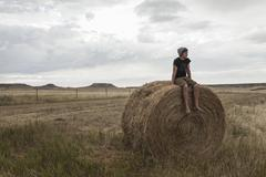 Teenage boy sitting on haystack in field, South Dakota, USA Stock Photos