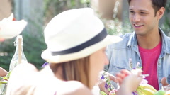 Young man eating brunch outdoors with friends Stock Footage