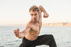 Mid adult man on beach in kung fu pose Kuvituskuvat