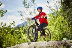 Young female bmx biker poised on edge of rock in forest Kuvituskuvat