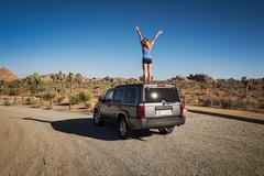 Runner jubilant standing on car, Joshua Tree National Park, California, US Kuvituskuvat