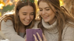 Young college students girls laughing while using tablet pc autumn fall BG - stock footage