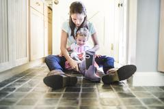 Mother and daughter putting on boots in kitchen - stock photo