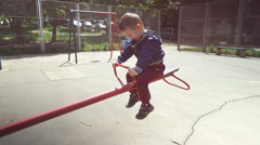 Little Kids Having Fun on Playground Rocker  Stock Footage