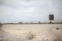 Freight train in desert landscape, California, USA Stock Photos