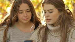 Two friends listening streaming music on smart phone device autumn fall Stock Footage