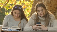 Two students working one texting on phone other reading text book autumn fall Stock Footage