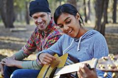 Young couple in forest playing acoustic guitar, Los Angeles, California, USA Stock Photos