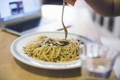 Young woman at table eating plate of noodles, focus on food Stock Photos
