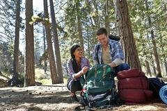 Young couple unpacking camping rucksack in forest, Los Angeles, California, USA Stock Photos