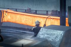 Steelworker measures red hot steel in forging press in steelworks - stock photo