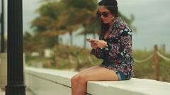 Woman checking her cellphone as she sits on cement wall by beach Stock Footage