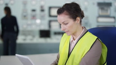 4K Smiling worker in power plant control room, looking at computer tablet Stock Footage