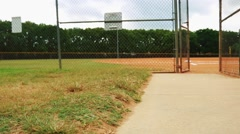 Steadicam shot of a baseball field taken from behind fence - stock footage