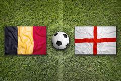 Belgium vs. England flags on soccer field - stock illustration