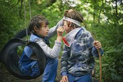 Boy face painting friend whilst playing in forest - stock photo