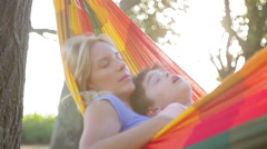 Mother and young son napping together in hammock - stock footage