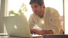 Man talk on cell phone while typing on laptop computer Stock Footage