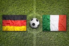 Germany vs. Italy flags on soccer field - stock photo