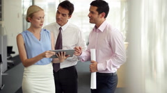 Business associates using digital tablet during casual meeting Stock Footage