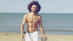 Happy athletic male model taking off shirt slow motion while walking towards - stock footage