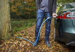 Man charging electric car in forest Stock Photos