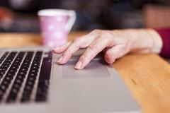 Senior woman using laptop, focus on hands Stock Photos