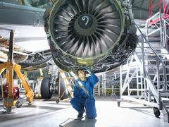 Engineer inspecting jet engine in aircraft maintenance factory - stock photo